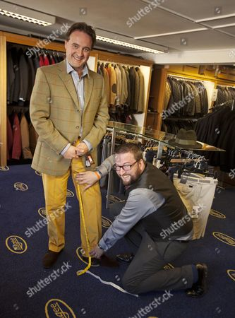 Stock Photo of Daily Mail Feature Writer Guy Walters Is Measured By Richard Cole One Of The Owners Of The Famous Gentleman's Outfitters In Cheltenham Which Is Closing Down After 126 Years.