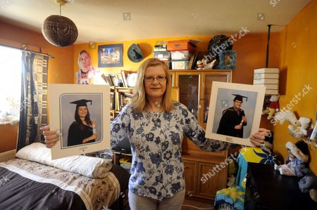 Ingrid Loyau-Kennett in her daughter's old bedroom holding photos of her son and daughter