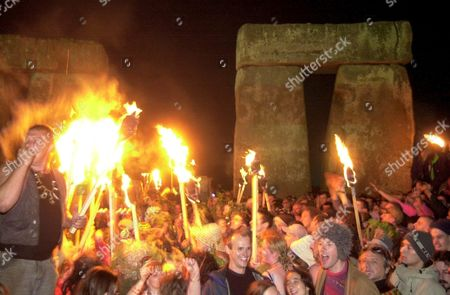 REVELLERS WAVE FLAMING TORCHES AT THE SUMMER SOLSTICE CELEBRATIONS AT STONEHENGE