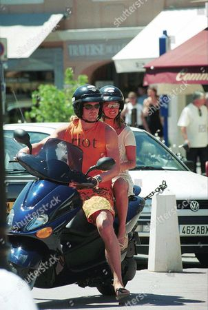EMMANUEL PETIT ON HOLIDAY WITH WIFE AGATHE DE LA FONTAINE, RIDING A SCOOTER