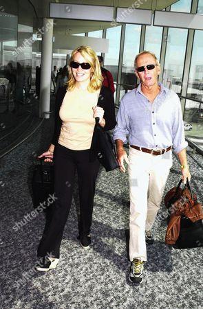 PAUL HOGAN WITH WIFE LINDA KOZLOWSKI ARRIVING AT HEATHROW AIRPORT