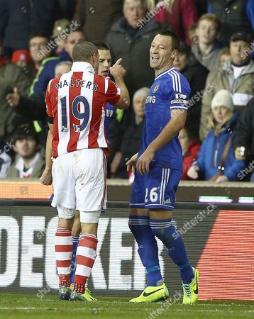 Stock Photo of Jonathan Walters of Stoke City pushes a smiling John Terry of Chelsea and is booked