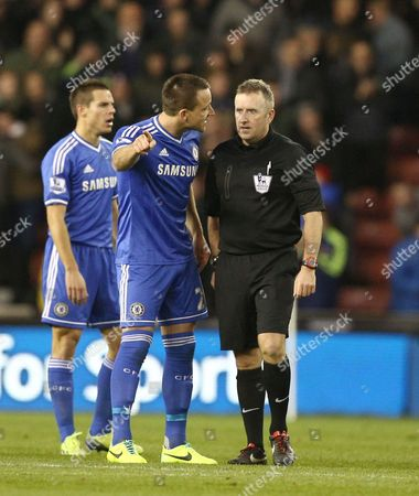 John Terry of Chelsea argues with referee Jon Moss after Cesar Azpilicueta of Chelsea appeared to be fouled by Jonathan Walters of Stoke City in the build up to Stoke City's second goal
