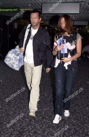ERIC CLAPTON ARRIVING AT HEATHROW AIRPORT FROM LOS ANGELES WITH GIRLFRIEND MELIA MCENERY AND THEIR NEW BABY JULIA / JULIE ROSE (born in June 2001)