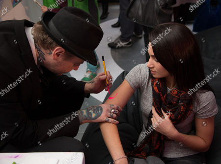 Stock Picture of Tattoo artist Dan Gold works on Laura Wright