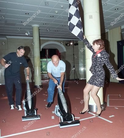 STIRLING MOSS WINNING A VACUUM CLEANER RACE AGAINST FOOTBALLER GARY MABBUTT WITH WRITER KATHY LETTE WAVING THE CHEQUERED FLAG