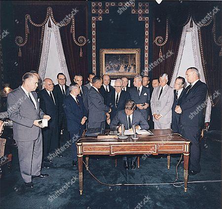 Signing of the Nuclear Test Ban Treaty in the White House Treaty Room on October 7, 1963. (center) U.S. President John F. Kennedy. (first row) Senator John Pastore, Senator J.W. Fulbright, Senator George Aiken (R-Vermont) , Senator Everett Dirksen (R-Illinois), Senator Leverett Saltonstall, Senator Thomas H. Kutchel, Vice President Johnson. (second row) unidentified man, Senator Mike Mansfield (D-Montana) , John J. McCloy, unidentified man, W. Averell Harriman, Senator George Smathers, U.S. Secretary of State Dean Rusk, Senator Hubert Humphrey (D-Minnesota) , William C. Foster, Senator Howard W. Cannon.