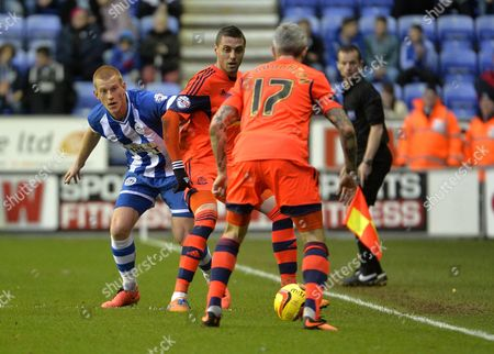Ben Watson of Wigan Athletic competes for the ball with Andre Moritz and Kevin McNaughton of Bolton Wanderers
