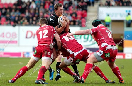 Ashley Beck of Ospreys is tackled by Scott Williams and Rhys Priestland of Scarlets