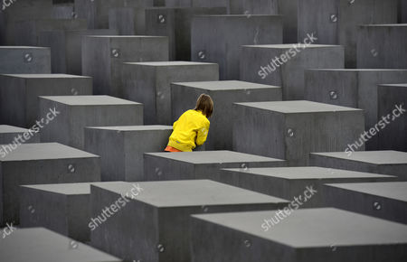 Memorial to the Murdered Jews of Europe, child playing hide and seek at the Holocaust Memorial designed by architect Peter Eisenman