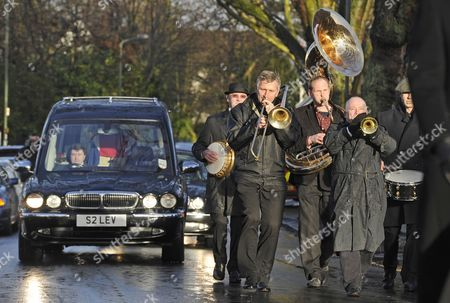 The hearse following behind a brass band