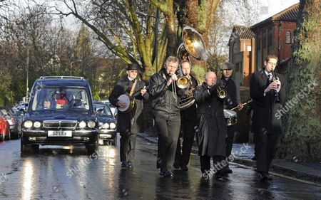 Stock Photo of The hearse following behind a brass band