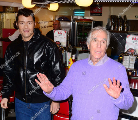 (L-R) Ben Freeman, Henry Winkler, hands over the iconic leather jacket to Freeman, who is among cast of Happy Days, anew musical produced by Amy Anzel, set to premiere at Bromley's Churchill Theatre, at Eds Easy Diner, Trocadero, 19 Rupert Street on January 8, 2014, in London, England.