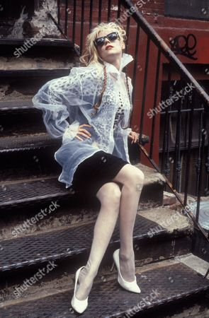 Singer Phoebe Legere, sitting on outdoor steps. New York, USA, 1986