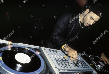 DJ Roger Sanchez wearing Kangol flatcap backwards and neatly trimmed goatee, UK 1990s