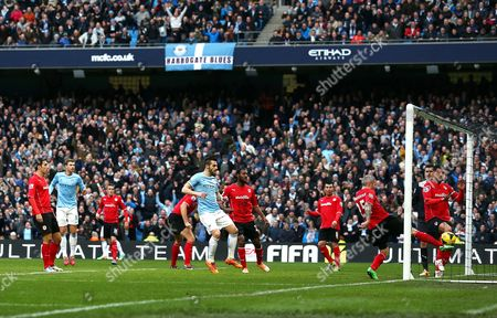 Kevin McNaughton of Cardiff City clears the ball from the shot by Edin Dzeko of Manchester City but goal technology showed it was over the line 1-0