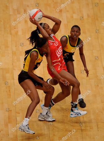 Sasha Corbin of England Netball is surrounded by several Jamaica players