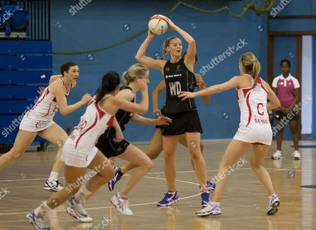 Katrina Grant of New Zealand holds the ball under pressure from Sara Bayman of England A