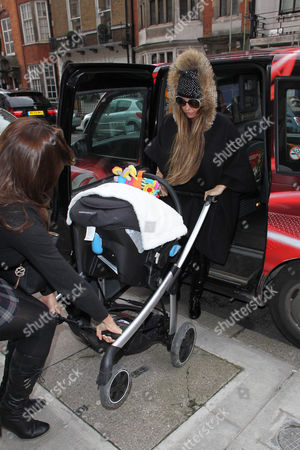 Katie Price getting out of a black cab with baby son Jett in a pushchair with son Jett Riviera
