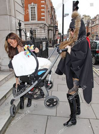 Katie Price is given help carrying baby son Jett up some steps in a pushchair with son Jett Riviera
