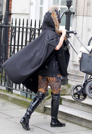 Stock Image of Katie Price is given help carrying baby son Jett up some steps in a pushchair with son Jett Riviera