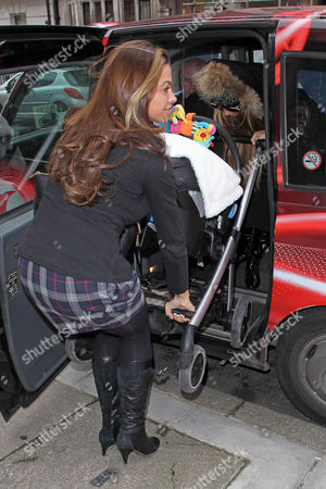 Stock Picture of Katie Price pulling baby son Jett into a black cab with son Jett Riviera