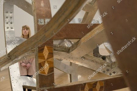 A member of staff looks at artwork by Richard Deacon