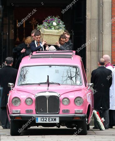 The coffin is carried out of the church to a pink hearse