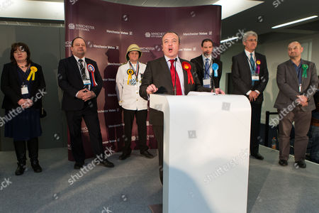 Labour Party candidate Mike Kane (front centre) delivers his victory speech as other candidates - L-R Mary Di Mauro (Liberal Democrats), Eddy O'Sullivan (BNP), Captain Chaplington-Smythe (Monster Raving Loony Party), Reverend Daniel Critchlow (Conservatives), John Bickley (UKIP) and Nigel Woodcock ( GREEN Party) - stand behind