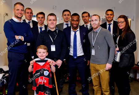 Ollie, Tony, James Mills, Laura pose with the QPR team in the home dressing room - QPR fan Mills was recently diagnosed with terminal brain cancer and was presented with VIP tickets to what may be his last ever match by Joey Barton who personally delivered the tickets to his home in Eastbourne earlier in the week