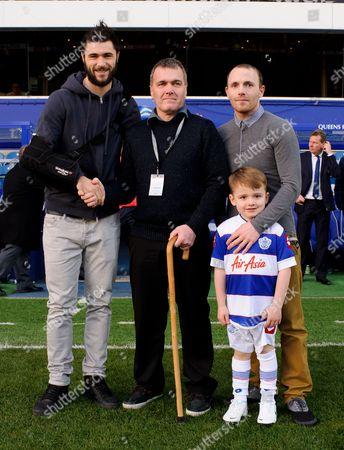 Charlie Austin of QPR chakes hands with Tony Mills who stands with sone James and grandson Ollie - QPR fan Mills was recently diagnosed with terminal brain cancer and was presented with VIP tickets to what may be his last ever match by Joey Barton who personally delivered the tickets to his home in Eastbourne earlier in the week