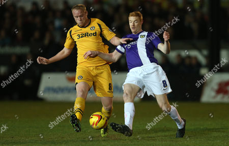 Newport's Lee Minshull is challenged by Oxford's Dave Kitson