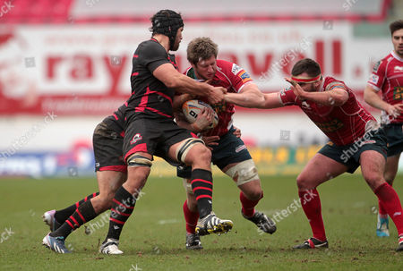 Richard Kelly of Scarlets is tackled by Andries Strauss and Izak van der Westhuizen of Edinburgh