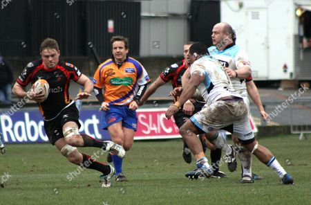 Lewis Evans of Newport Gwent Dragons dodges a challenge from Jerry Yanuyanutawa of Glasgow Warriors