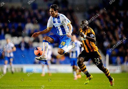 Leonardo Araujo Ulloa of Brighton & Hove Albion leaps to control the ball as Abdoulaye Faye of Hull City chases
