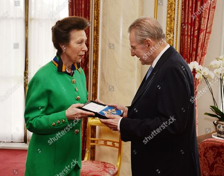 Princess Anne presents former IOC (International Olympic Committee) President Jacques Rogge with his insignia of KCMG (Knight Commander of the Order of Saint Michael and Saint George), during a small private Investiture ceremony attended by family and friends, in the Bow Room at Buckingham Palace