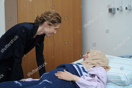 Syria's First Lady Asma al-Assad talks to a patient during her visit to the Obstetrics hospital in Damascus on the occasion of International Women's Day