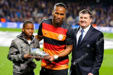 Didier Drogba of Galatasaray and his son receive a silver boot from Chelsea Chief Executive Ron Gourlay