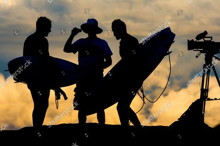 Mark Matthews, Tim Bonython and Dan Ross in silhouette discuss the day's events