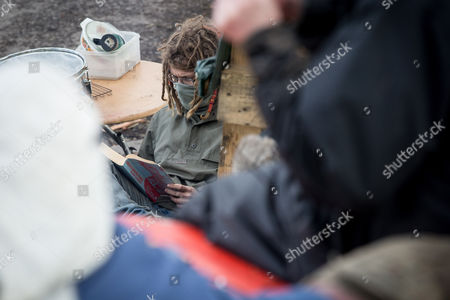 Stock Picture of A protester at the camp reads 'Understanding Power' by Noam Chomsky