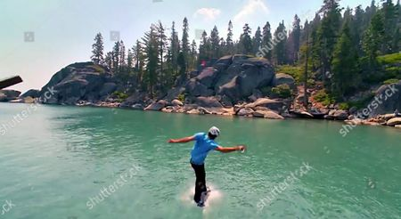 Stock Photo of Pro skater Bob Burnquist enters the water after skate boarding off the floating skate ramp