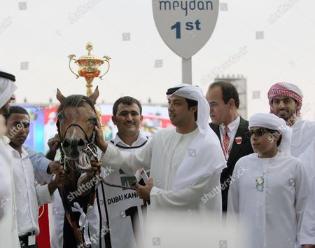 Stock Photo of Sheikh Mansour bin Zayed bin Sultan Al Nahyan pets Rabbah de Carrere after it won the Kahayla Classic as part of Dubai's World Cup at Meydan race track