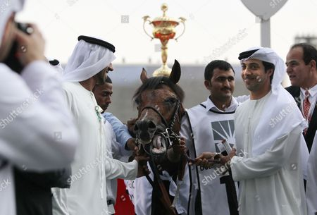 Stock Image of Sheikh Mansour bin Zayed bin Sultan Al Nahyan pets Rabbah de Carrere after it won the Kahayla Classic as part of Dubai's World Cup at Meydan race track