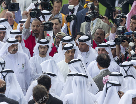 Sheikh Mansour bin Zayed bin Sultan Al Nahyan (Center) stands next to Sheikh Saif bin Zayed Al Nahyan as they attend horse races at Dubai's World Cup at Meydan race track