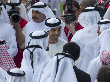 Sheikh Mansour bin Zayed bin Sultan Al Nahyan (center) stands next to Sheikh Mohammed bin Rashid Al Maktoum (face hidden) as they attend horse races at Dubai's World Cup at Meydan race track