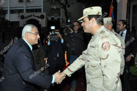 Egypt's interim President Adly Mansour (L) shaking hands with Egypt's army chief Field Marshal Abdel Fattah al-Sisi (R), after his meeting with members of the Supreme Council of the Armed Forces