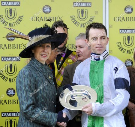 Jockey Leighton Aspell picks up the trophy from Princess Anne