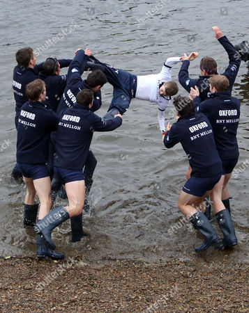 Stock Photo of Oxford University Blue boat are seen throwing their cox Laurence Harvey into the River Thames to celebrate their victory