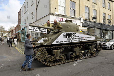 Tony Miles, (white hair and glasses) aka Smiley Miley from the Radio 1 Roadshow, rides in a WW2 Sherman tank through local streets in a protest by residents and traders from Clifton Village in Bristol about plans for a Residents Parking Scheme in their area from Bristol's elected Mayor, George Ferguson.