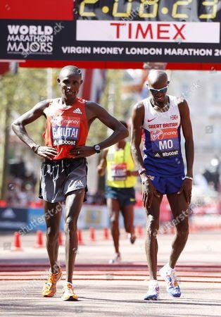 Mo Farah (R) finishes 8th, next to Kenya's Geoffrey Mutai after finishing the Virgin Money London Marathon 2014